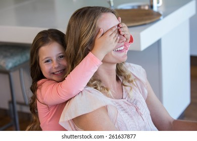 Happy little girl covering her mother eyes at home