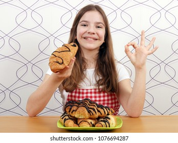 happy little girl with croissants and ok hand sign