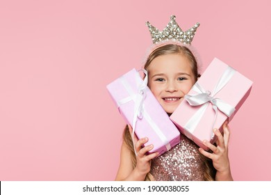 happy little girl in crown holding wrapped presents isolated on pink