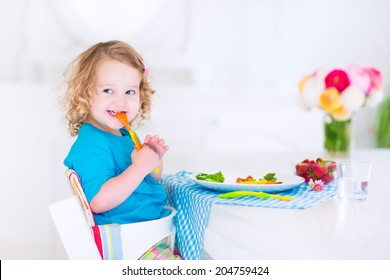 Happy little girl, cute curly toddler, eating fresh vegetables for lunch, healthy salad snack, corn, broccoli, carrots and strawberry fruit in a white dining room sitting in a high chair
