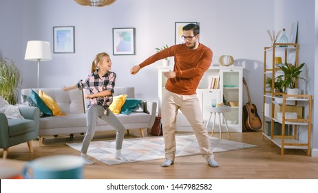 Happy Little Girl Dances with Young Father in the Middle of the Living Room. Happy Family Time, Father and Daughter Dancing at Home. - Shutterstock ID 1447982582