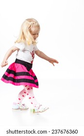 Happy little girl dancing on white background