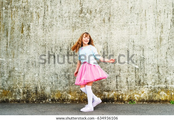 Happy little girl dancing on the street, wearing beautiful tutu skirt and high over knee socks