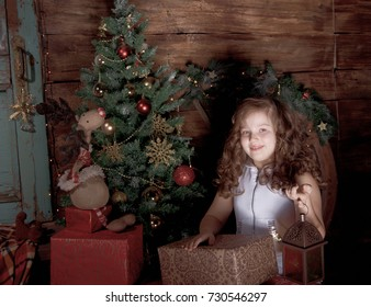 Happy little girl  decorate Christmas tree in beautiful living room with traditional fire place.