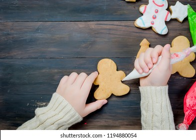 Happy little girl  decorating a christmas gingerbread  cookies using colored  glazeon dark wooden table, top view