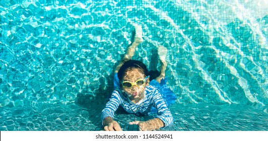 Happy little girl dive underwater in swimming pool.Happy child playing in the swimming pool with summer vacation.Kids learn to swim or Healthy lifestyle concept.