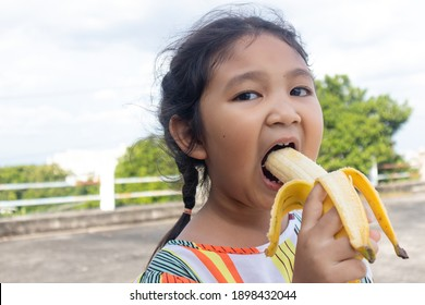 Happy Little girl eating bananas with deliciousness, bananas are high-vitamin foods.
