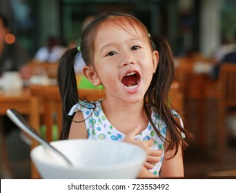 Happy little girl eating breakfast in the restaurant at the morning.
