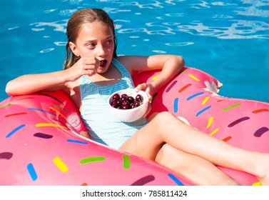 Happy little girl eating cherries on a colorful inflatable donut in a  swimming pool.