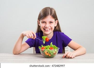 Happy little girl is eating salad.