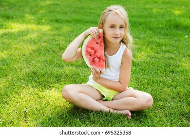 Happy little girl eating watermelon on the grass in summertime