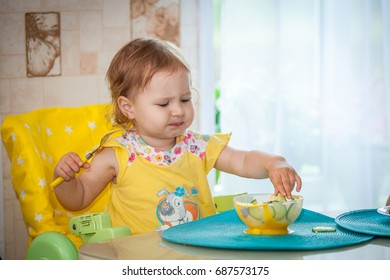 Happy little girl eats a healthy dinner at the table