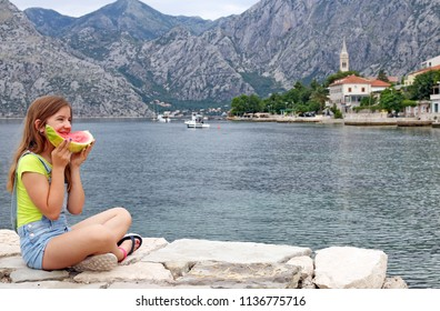 happy little girl eats a watermelon on a summer vacation Kotor bay