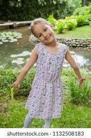Happy Little Girl in elegant dress at park, smiling portrait of child outdoor