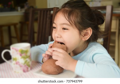 a happy little girl enjoy eating homemade chocolate bun in kitchen, filtered tones