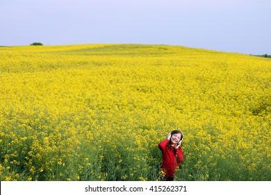 happy little girl enjoy in music on yellow field summer season