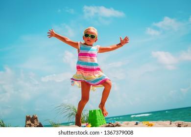 happy little girl enjoy play with toys on beach