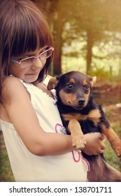 Happy little girl with eye glasses holding her puppy. Warm effect edition.
