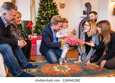 Happy little girl with family unboxing gift on Christmas day at home. Playful festive situation with blonde funny girl holding a present. Christmas and holidays concepts
