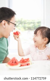 happy little girl with father eating fruits