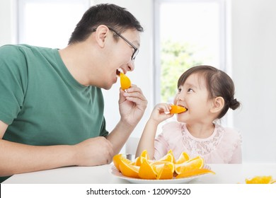 happy little girl with father eating orange