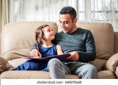 Happy Little Girl And Father Are Enjoying Reading Book Together