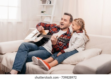 happy little girl with father playing guitar and looking away at home