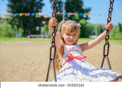 Happy little girl five years old wearing summer dress having fun on a swing in the park on a hot sunny summer day
