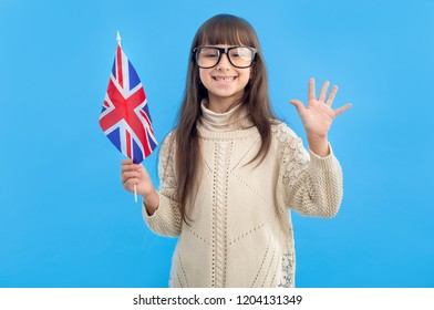 Happy little girl with flag of Great Britain shows five fingers of her hand standing on a blue background. Learn English.
