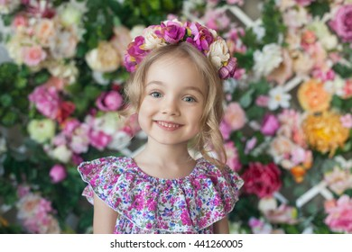 Happy little girl in a flower wreath smiling