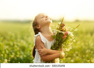 Happy little girl with flowers in the field