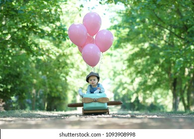 happy little girl flying her airplane with pink balloons and having fun