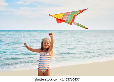 Happy little girl with flying kite on tropical beach. Beach fun, childhood concept