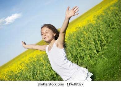 Happy little girl in front of canola field