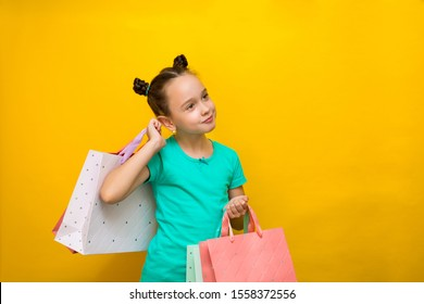 happy little girl with funny tails standing isolated over yellow background holding shopping bags. smiles thoughtfully.