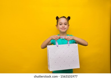 happy little girl with funny tails standing isolated over yellow background holding shopping bags. Looking camera.