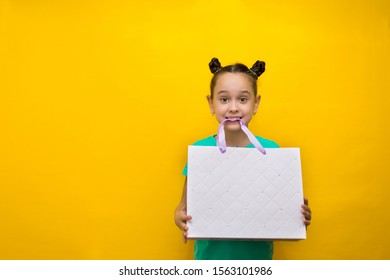 happy little girl with funny tails standing isolated over yellow background holding package in her teeth. Looking camera.
