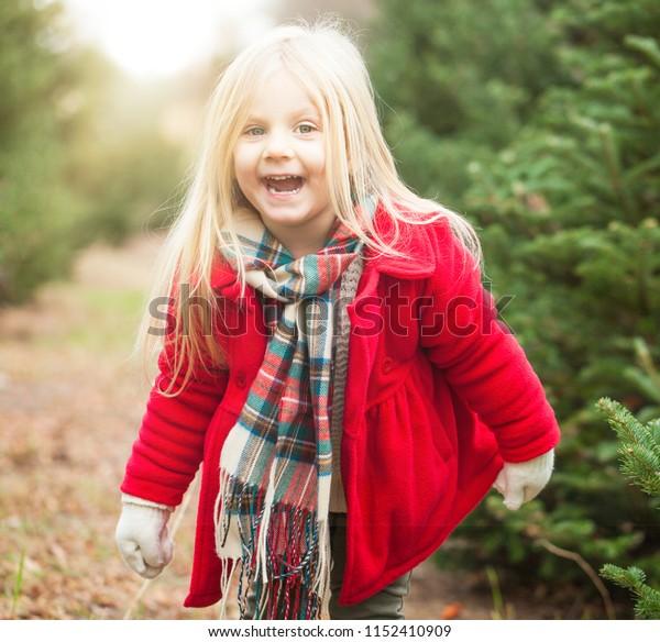 Happy little girl in fur tree farm. Joyful expression. Happiness concept