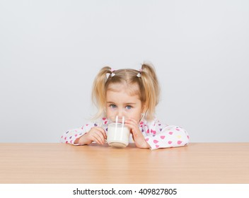 Happy little girl with a glass of milk. At the table on white background.