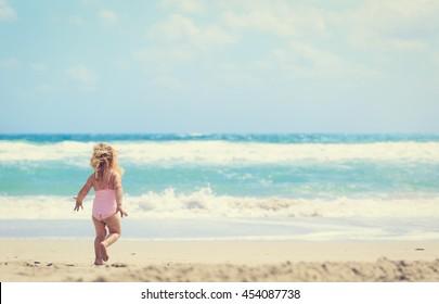 happy little girl going to swim at beach