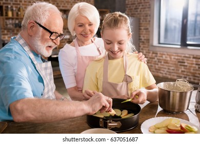 Happy little girl with grandparents preparing apple pie at kitchen table