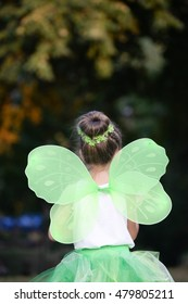 Happy little girl in a green fairy costume with wings