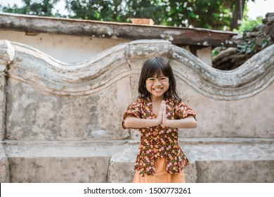 Happy little girl greeting in traditional way from indonesia with both hands gesture