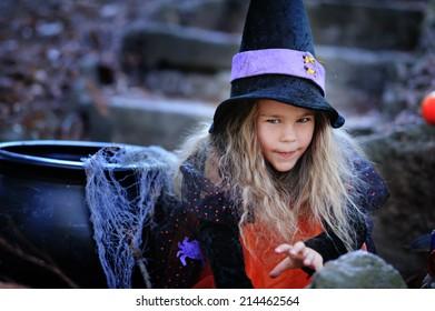 happy little girl in halloween costume with jack pumpkin tick or treat