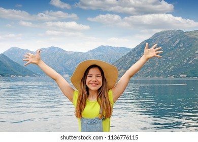 happy little girl with hands up on summer vacation