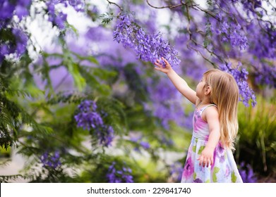 happy little girl has a fun in blossom jacaranda garden