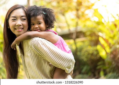 Happy little girl having fun with parent Asian or Child care staff at park on holiday. mother ther carrying daughter on back outdoors. Mother's Day. family, Volunteer,Orphan Care Organization concept
