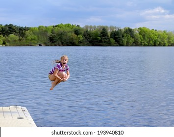 Happy little girl having fun on the lake. Jumps