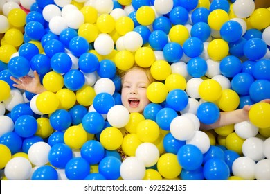 Happy little girl having fun in ball pit in kids indoor play center. Child playing with colorful balls in playground ball pool. Activity toys for little kids.