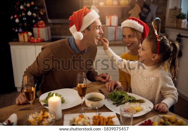 Happy little girl having fun and feeding her father while having Christmas lunch at dining table.